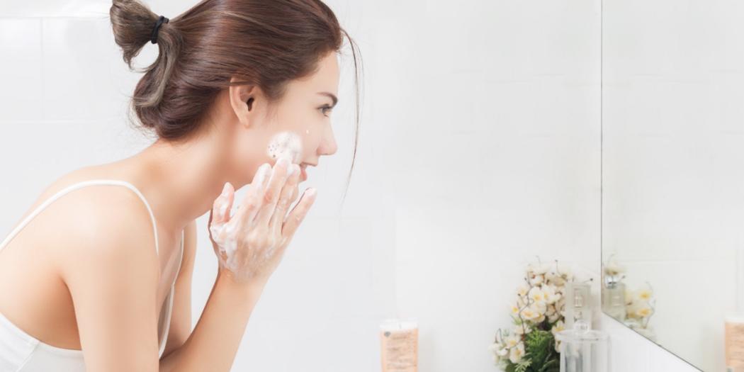 Kobieta w łazience przed lustrem myjąca twarz pianką do mycia twarzy