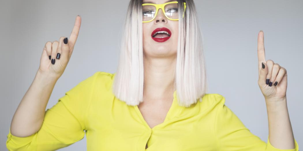 Kobieta w żółtej koszuli i żółtych oprawkach okularów z siwoblond włosami