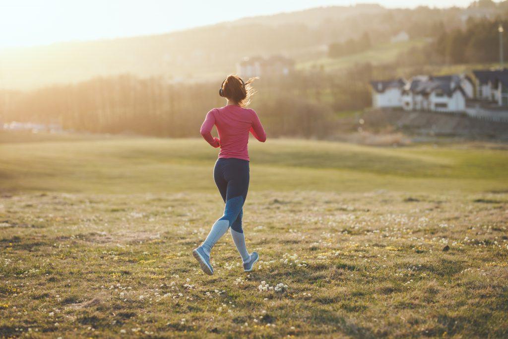 kobieta biegająca po kwitnących łakach