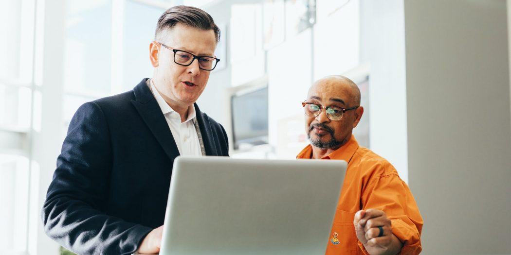 dwóch mężczyzn przy laptopie