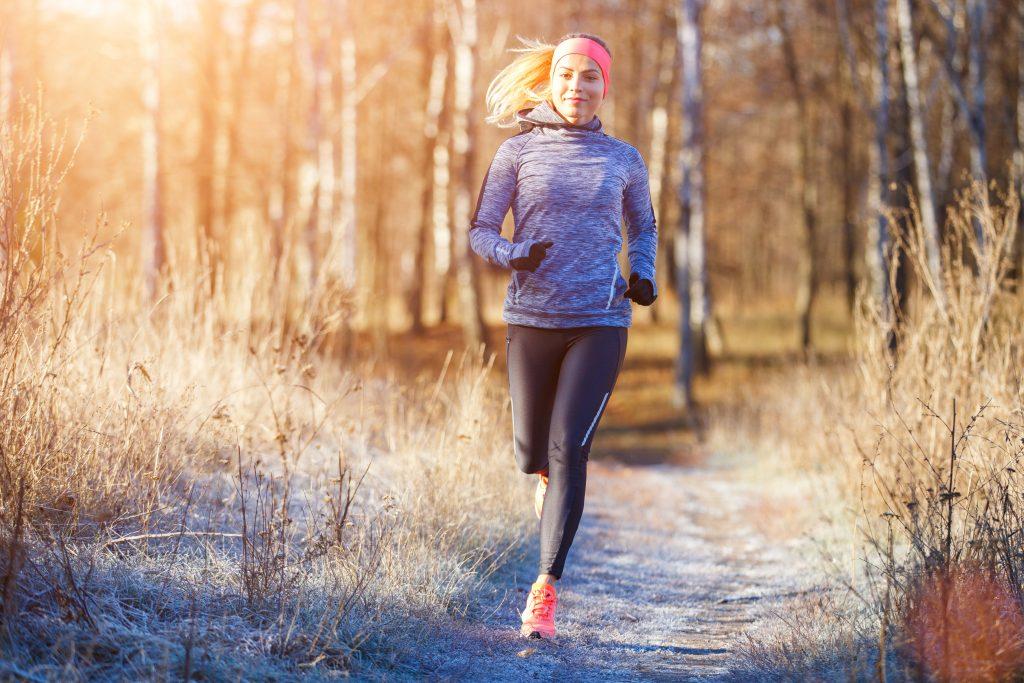 młoda dziewczyna biegająca zimą po lesie