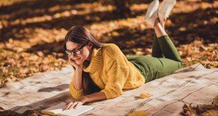 kobieta czytająca książke na kocyku jesienią
