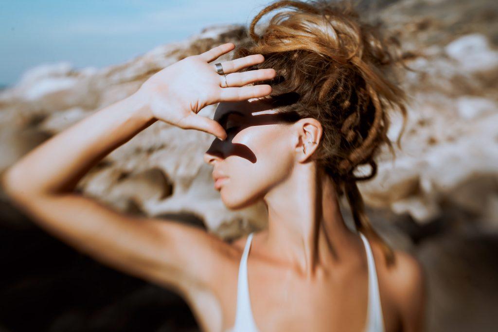 kobieta osłaniająca twarz od słońca