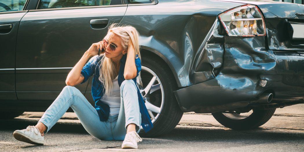 kobieta siedząca przy uszkodzonym samochodzie