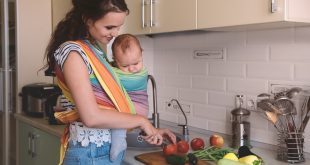 kobieta z dzieckiem w chuście przygotowująca obiad