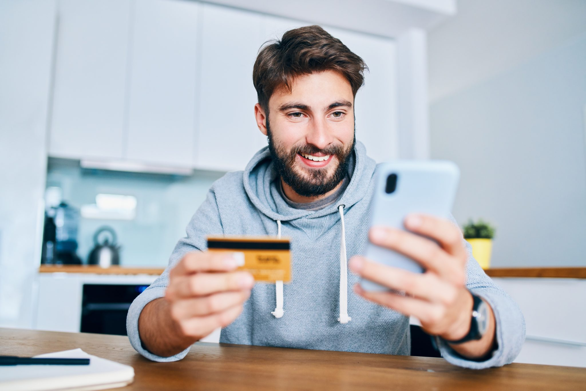 mężczyzna w domu z kartą kredytową i smartfonem