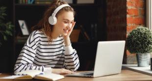kobieta w słuchawkach na uszach przed komputerem