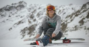 Mężczyzna zawiązujący na stoku buty snowboardowe