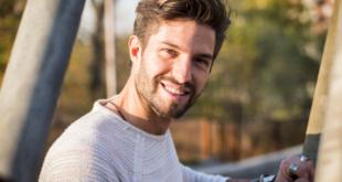 uśmiechnięty mężczyzna z bujnymi włosami i broda