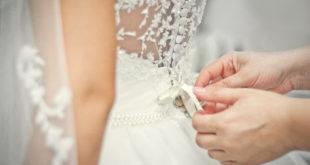 Kobieta zakładająca koronkową suknię ślubną