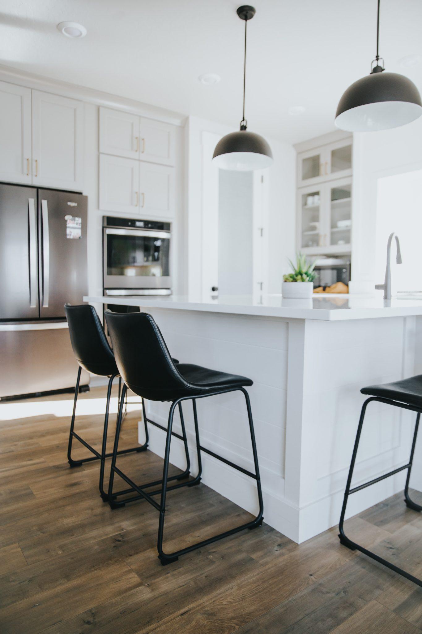 biała wyspa kuchenna z czarnymi krzesłami