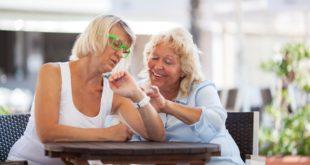 dwie dojrzałe kobiety sprawdzające godzinę na zegarku jednej z nich
