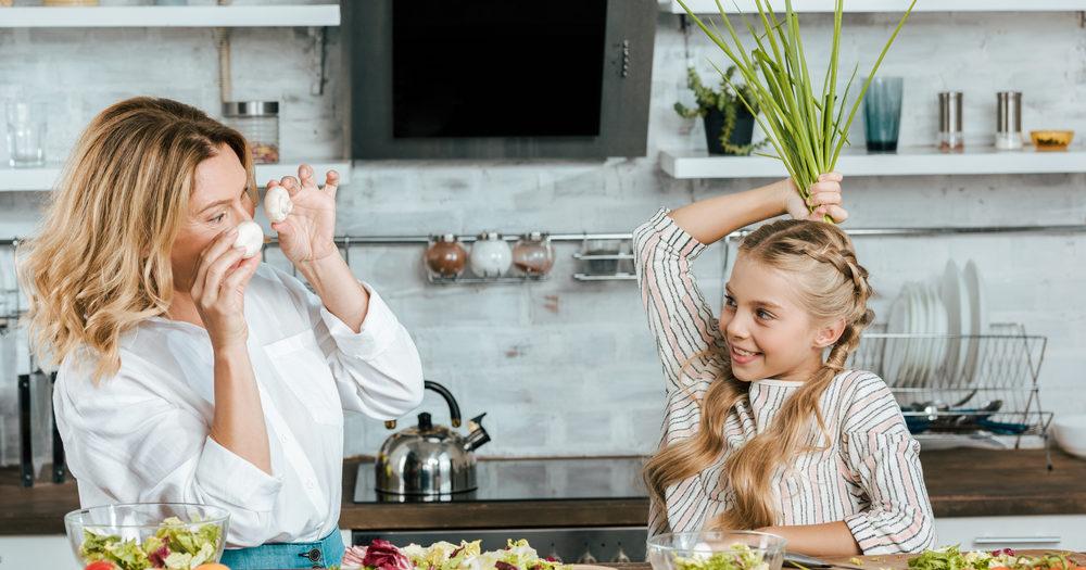 matka z córką przygotowujące posiłek w kuchni