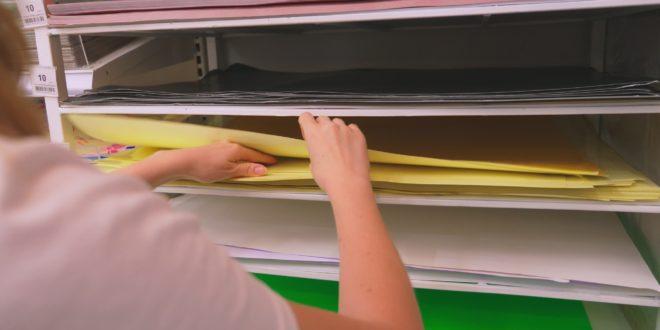Kolorowe kartki papieru ułożone na regale