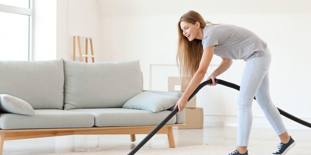 Kobieta odkurzająca podłogę odkurzaczem workowym