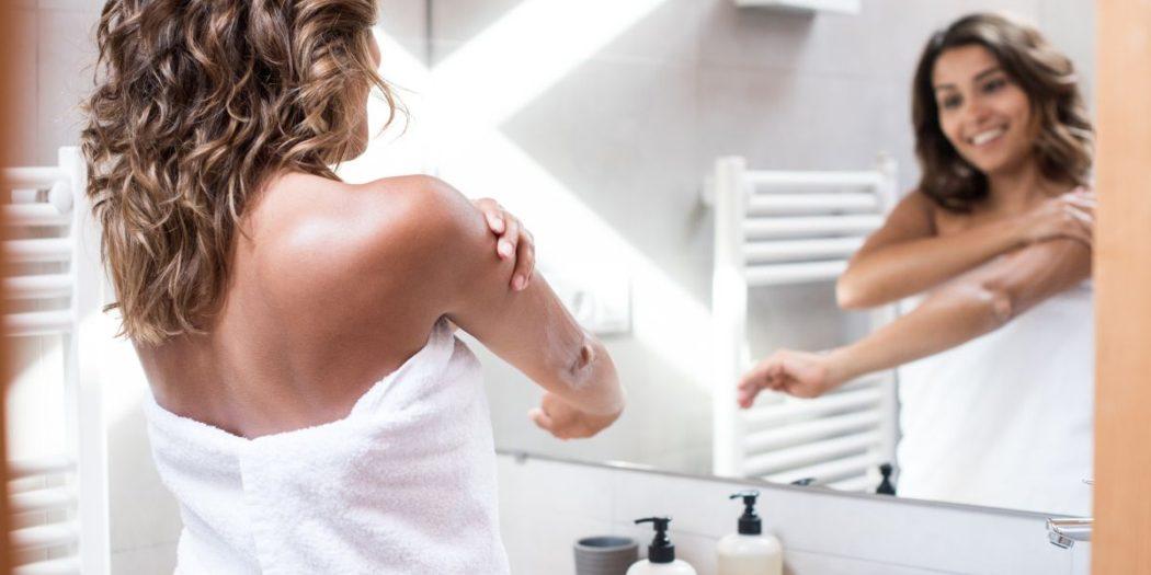 kobieta przed lustrem wcierająca balsam