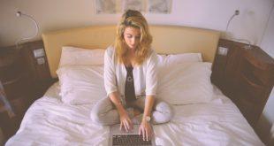 kobieta w łóżku robiąca zakupy przez internet