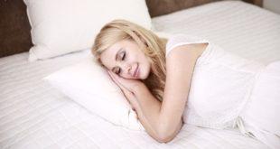 kobieta śpiąca w łóżku na białej pościeli