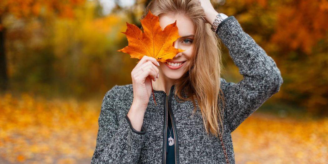 jesień kobieta w płaszczu z pomarańczowym liściem