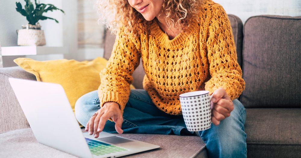 kobieta żółty sweter przed komputerem