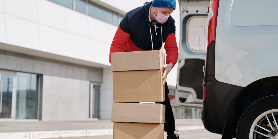 kurier w maseczce pakujący paczki na samochód