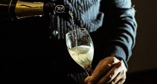 mężczyzna nalewający szampana do kieliszka