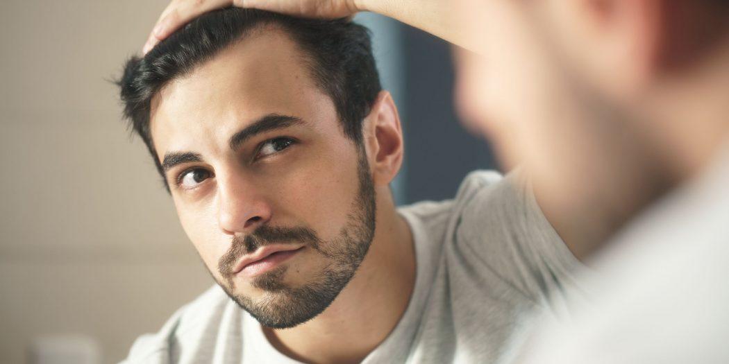 mężczyzna przeczesujący włosy