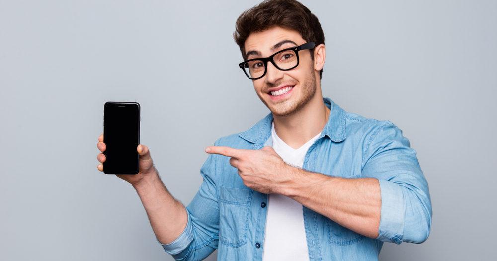 mężczyzna wskazujący na swojego smartfona