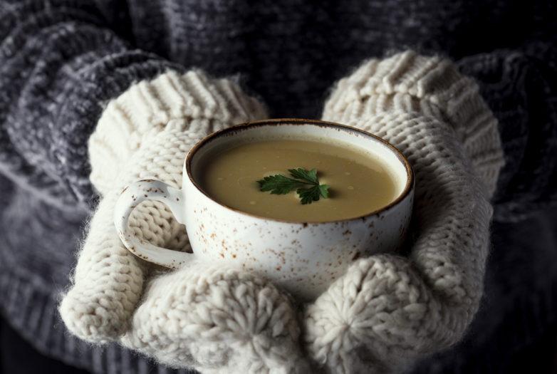 kobieta trzymająca rozgrzewającą zupę w rękawicach