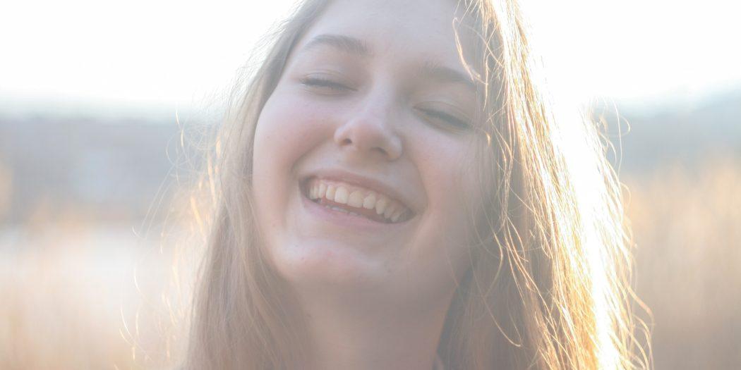 uśmiechnięta dziewczyna z długimi blond włosami