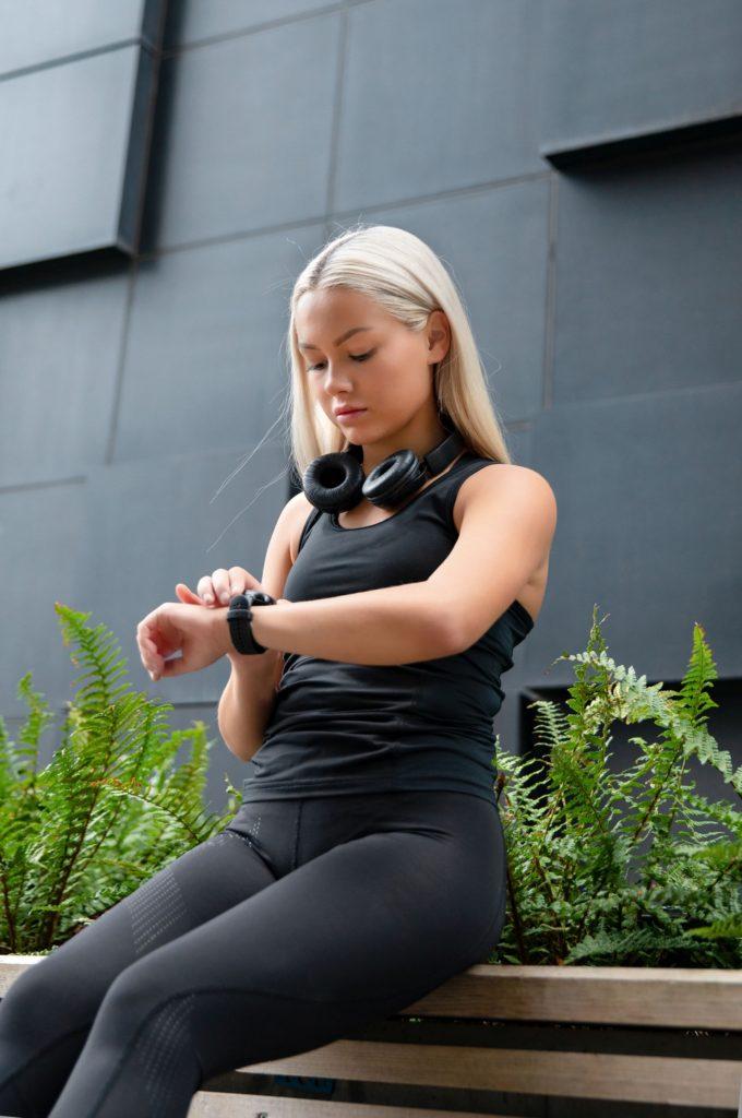 kobieta ubrana na sportowo sprawdza smart watcha
