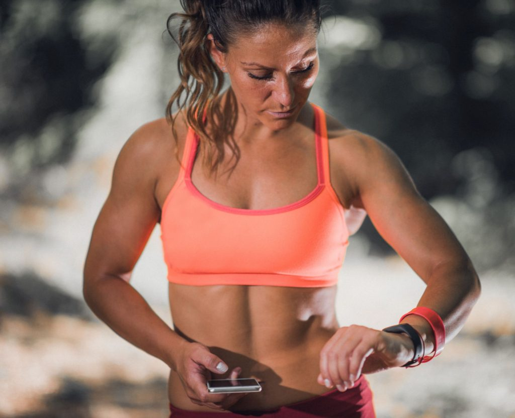 kobieta spoglądająca na smart watcha w trakcie treningu