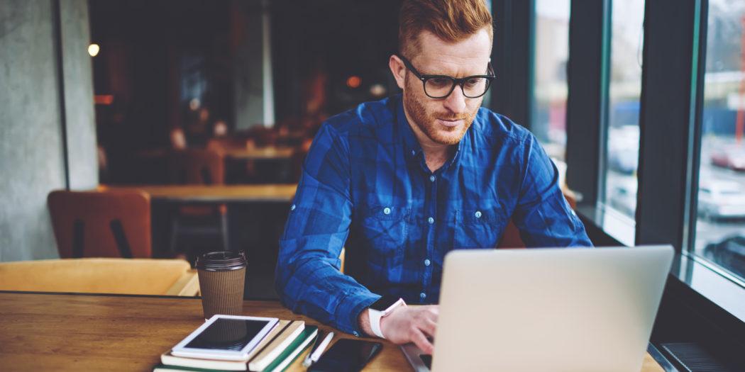 Mężczyzna wystawiający fakturę na laptopie w kawiarni