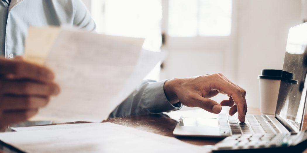 Mężczyzna wystawiający fakturę przed komputerem
