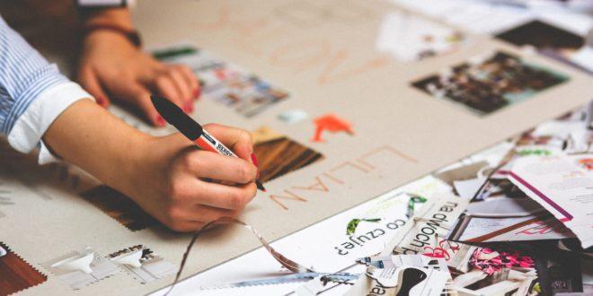 kobieta projektująca na papierze materiały graficzne