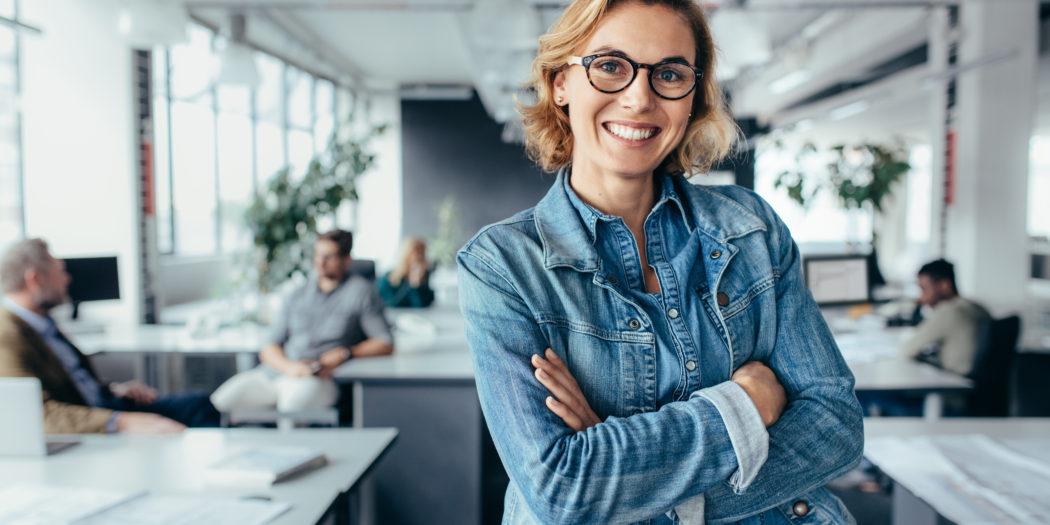 młoda zadowolona kobieta w pracy w biurze