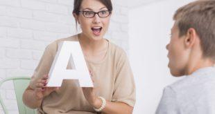 kobieta z białą literą A na zajęciach z logopedii z chłopcem
