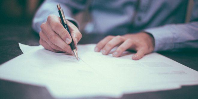 mężczyzna w koszuli podpisujący umowę