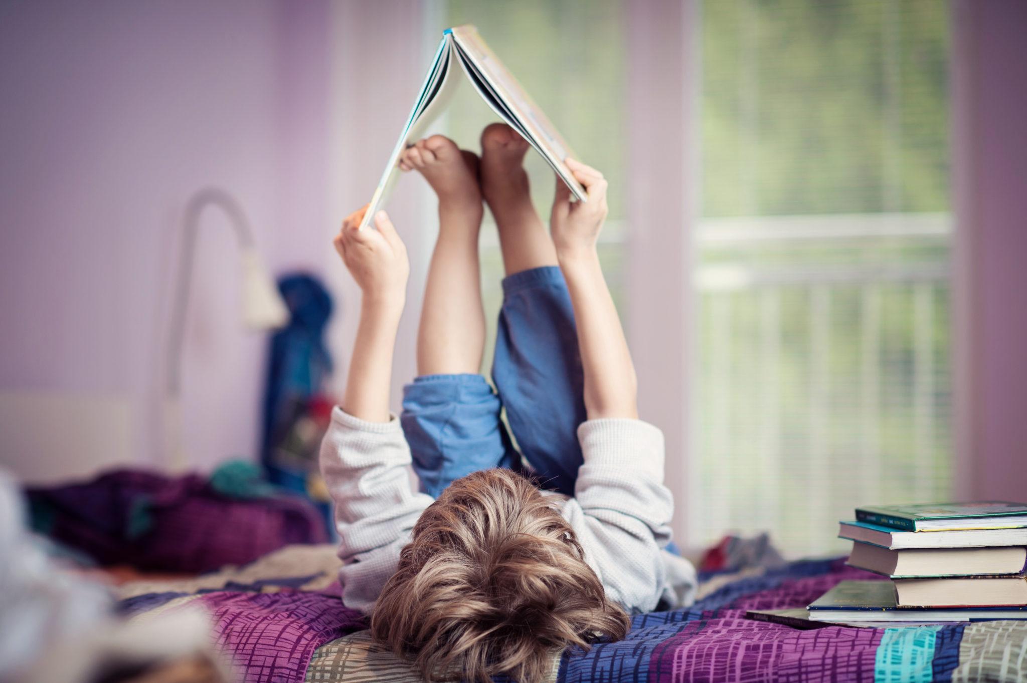 chłopiec na łóżku z książką