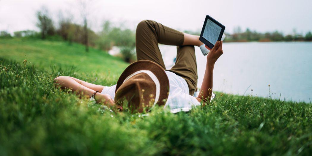 czytanie książki z czytnika nad jeziorem