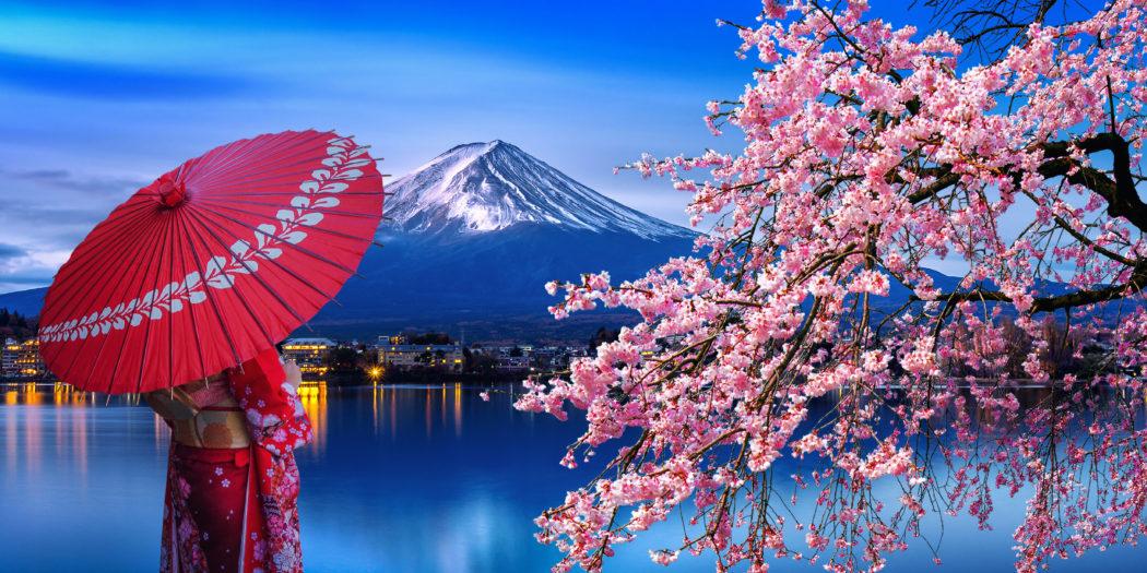 Japonia - kobieta w tradycyjnym kimonie na tle góry Fuji obok kwitnącej wiśni