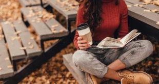 piękna kobieta czytająca jesienią ksiązkę na zewnątrz