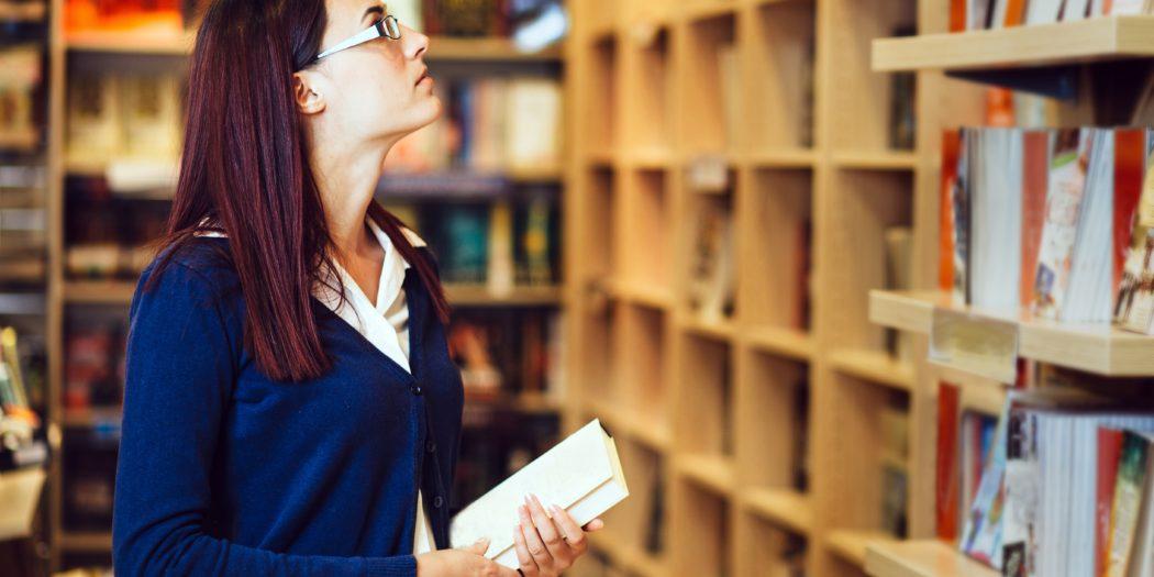 młoda kobieta szukająca książek w księgarni