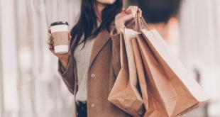 kobieta w beżowym płaszczu z kawą w ręku i z torbami zakupów