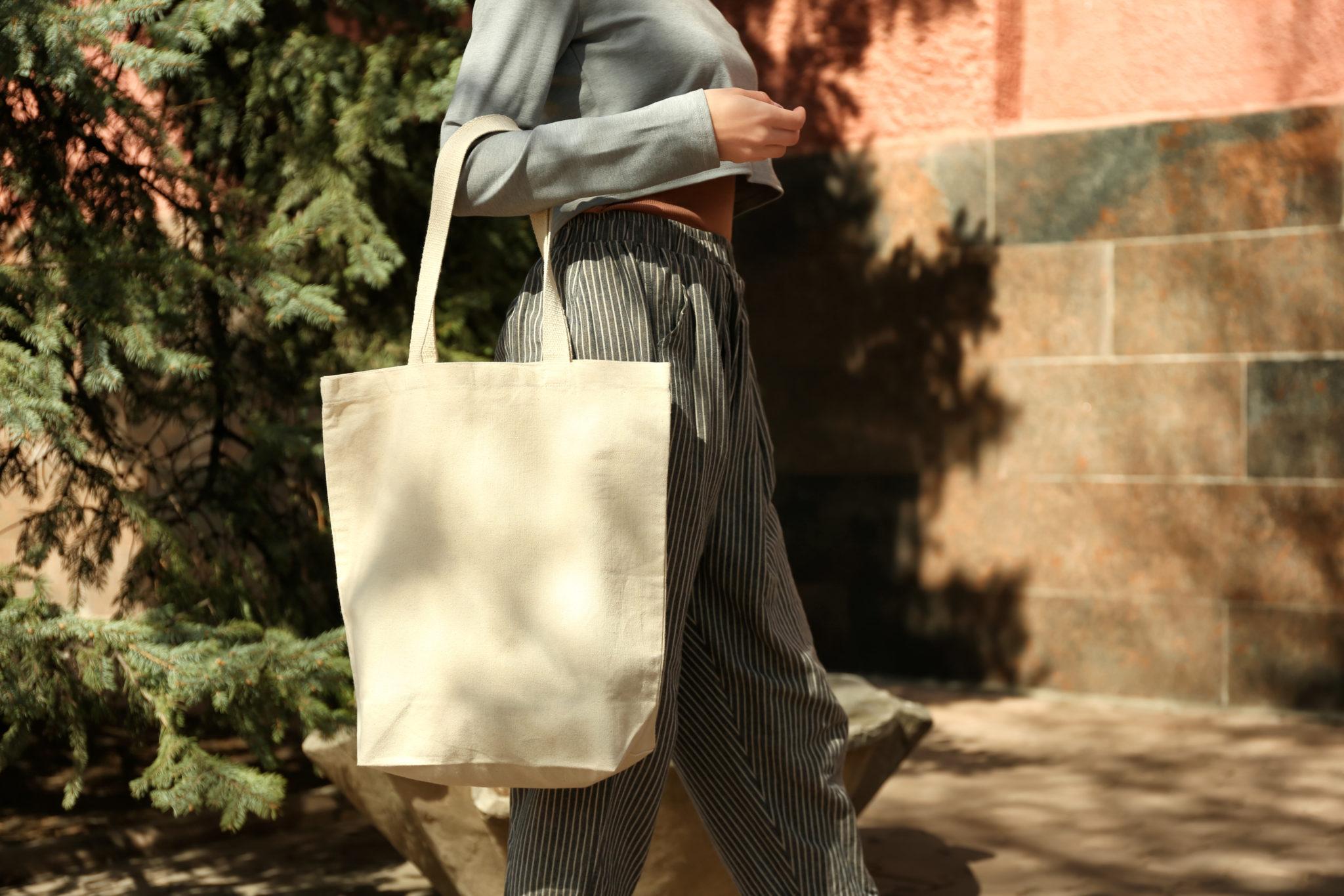 młoda kobieta idąca z bawełnianą torbą na zakupy