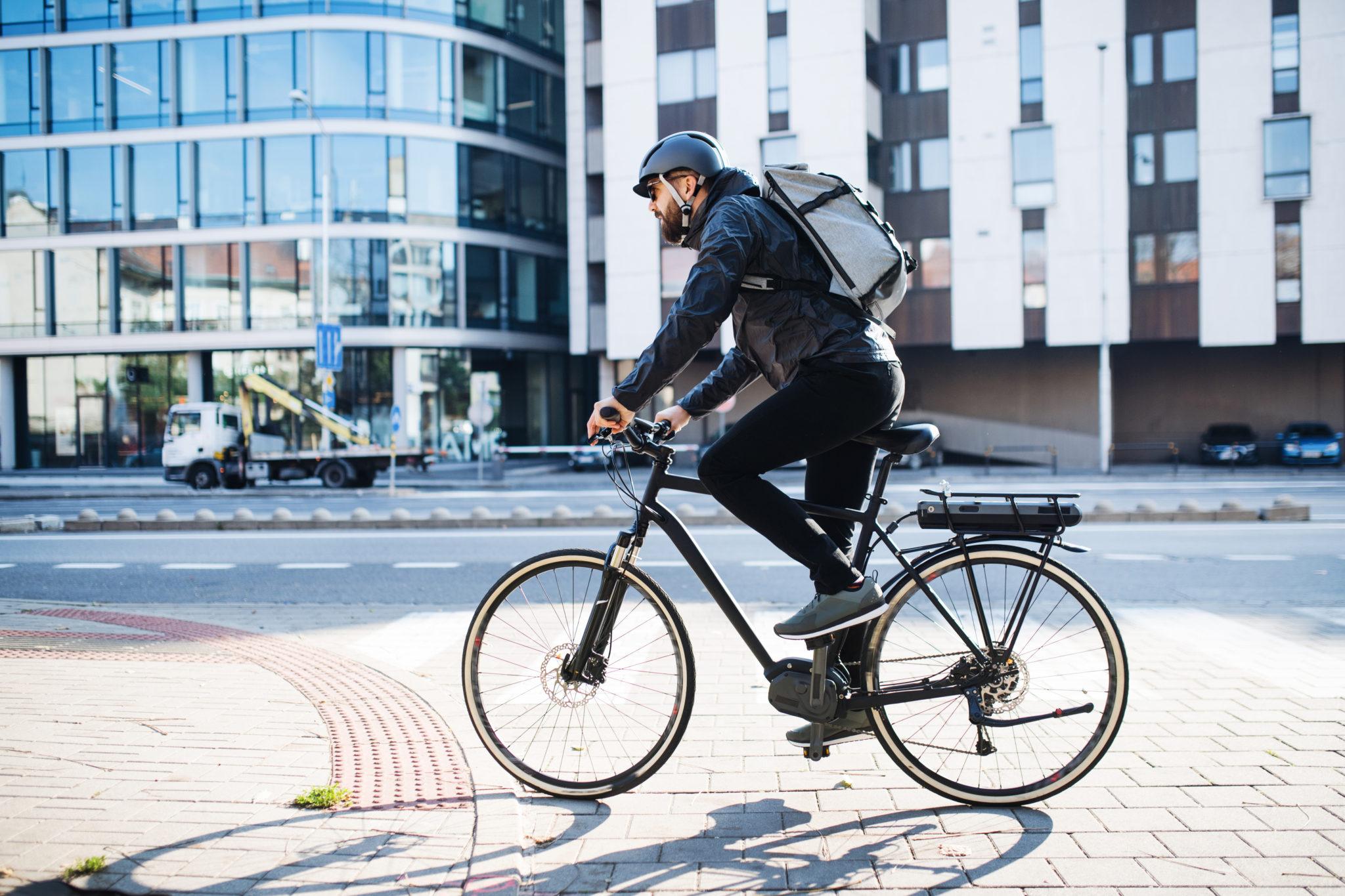 mężczyzna z plecakiem jadący do pracy na rowerze