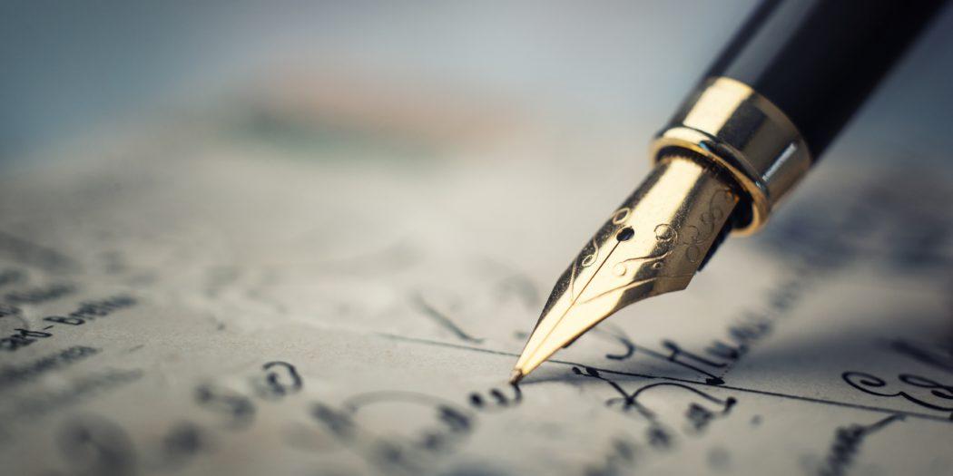 Stare ozdobne pióro piszące po papierze