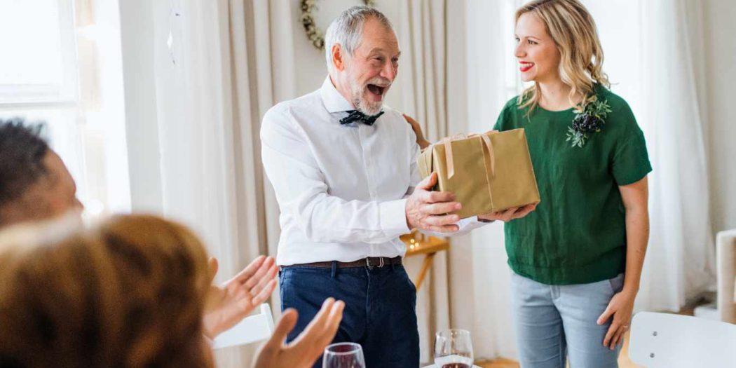młoda dziewczyna dająca prezent staruszkowi