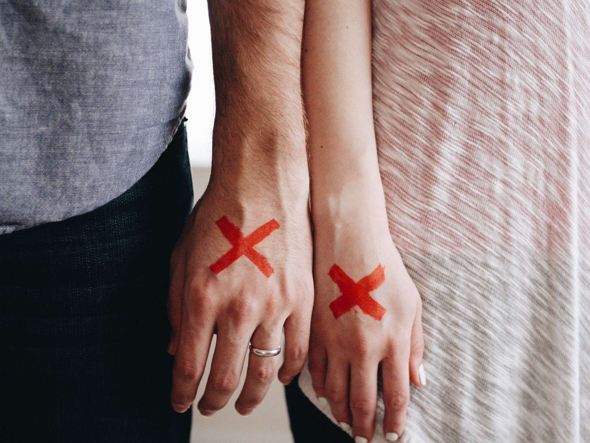 męska i damska dłoń z czerwonymi iksami rozpad związku