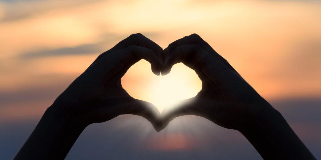 kształt serca z dłoni na tle zachodu słońca